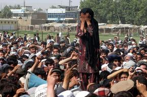 An Afghan girl whose family members were killed overnight after a raid by NATO and Afghan forces, covers her face as she weeps during a protest in Taloqan May 18, 2011. Ten people have been killed and fifty wounded in violent protests against the killing of two men and two women in a night-time raid in north Afghanistan, a top local health official said. REUTERS/Wahdat (AFGHANISTAN